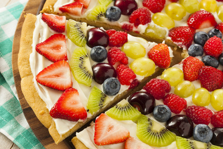 29947120 - homemade natural fruit pizza with frosting and berries