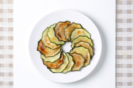 49880000 - circle of thin slices of roasted zucchini on a white plate