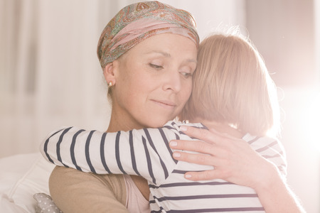 81576803 - worried woman with cancer cradles her child